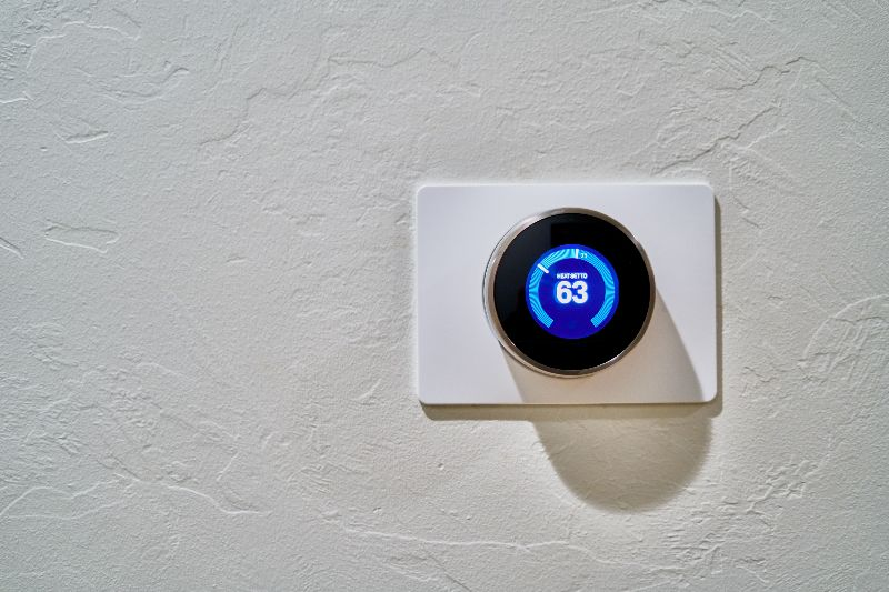 A Nest thermostat set to 63 degrees on a white wall