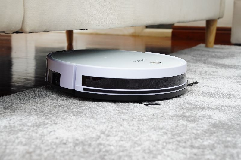 A white Roomba smart vacuum vacuuming a carpet under a couch
